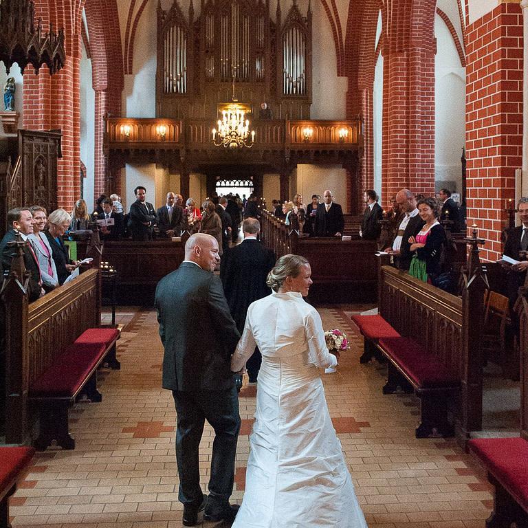 Hochzeitspaar Hand in Hand beim Auszug aus der Sankt Marien Kirche in Röbel an der Müritz in Mecklenburg Vorpommern beim Hochzeitsfotograf Landhochzeit Hamburg
