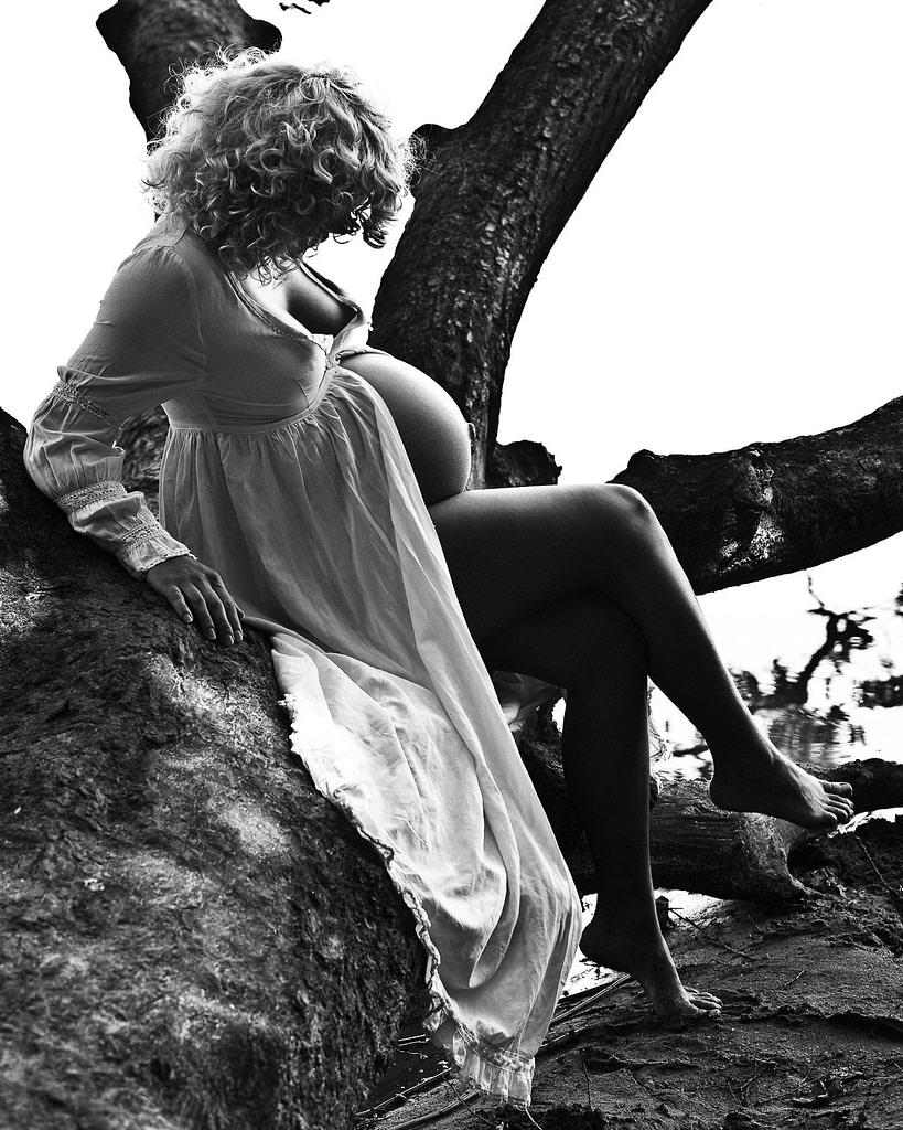 Schwangere im Kostüm auf Baum sitzend beim Babybauch Shooting in Hamburg draußen in der Natur