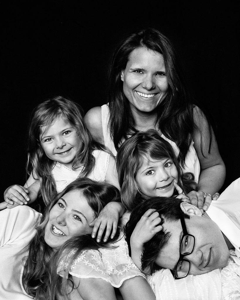 Zwillinge halten ihre großen Geschwister auf dem Schoss bei der Kinderfotografie in Hamburg Winterhude