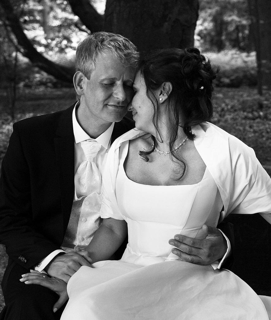 Braut und Bräutigam schmusen miteinander im Hamburger Stadtpark in Winterhude bei den Brautpaarfotos beim Hochzeitsfotograf Hamburg